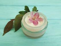 在木背景的奶油色化妆润湿的再生木兰花 库存照片