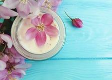 在木背景的奶油色化妆润湿的疗法再生产品秀丽木兰花 库存照片