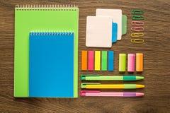 在木背景的学校和办公室文具 笔记本、笔记薄、笔、铅笔和材料 顶视图Flatlay 免版税库存照片