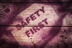 在木背景的安全第一标志 库存照片