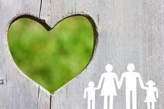 在木背景的家庭与绿色心脏 免版税库存图片