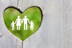 在木背景的家庭与绿色心脏 库存图片