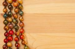 在木背景的小珠 免版税库存图片