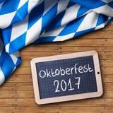 在木背景的巴法力亚桌布和有口号`慕尼黑啤酒节2017年`的一个黑板 免版税库存图片