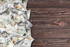 在木背景的很多美元 库存图片