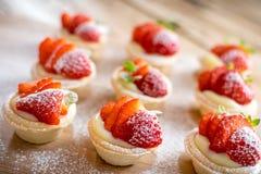 在木背景的微型草莓馅饼 免版税图库摄影