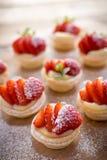 在木背景的微型草莓馅饼 库存图片
