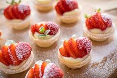 在木背景的微型草莓馅饼 免版税库存照片