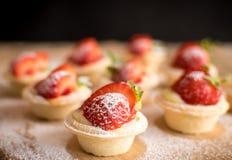 在木背景的微型草莓馅饼 免版税库存图片