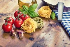 在木背景的意大利和地中海食品成分 西红柿面团、蓬蒿叶子和玻璃水瓶与橄榄油 库存图片