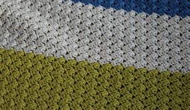 在木背景的手工制造五颜六色的被编织的羊毛毯子 免版税库存照片
