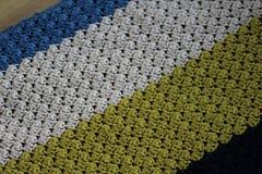 在木背景的手工制造五颜六色的被编织的羊毛毯子 库存图片