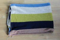 在木背景的手工制造五颜六色的被编织的羊毛毯子 免版税库存图片
