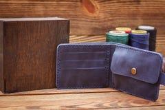 在木背景的手工制造皮革人钱包 免版税库存照片