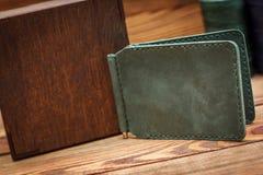 在木背景的手工制造皮革人钱包 图库摄影