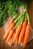 在木背景的新有机红萝卜束 免版税库存照片