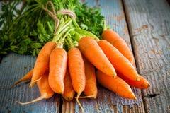 在木背景的新红萝卜束 免版税库存照片