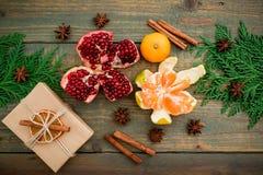 在木背景的新鲜的可口石榴石、柑橘、桂香和工艺礼物盒 概念新年度 平的位置 顶视图 库存照片