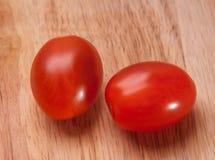 在木背景的新鲜的李子西红柿与自然阴影 顶视图 免版税库存照片