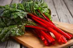 在木背景的新鲜的红色唐莴苣叶子 图库摄影
