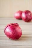 在木背景的新鲜的红洋葱 免版税图库摄影