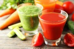 在木背景的新鲜的蕃茄、红萝卜和黄瓜汁 免版税库存图片