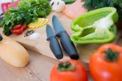 在木背景的新鲜蔬菜与刀子 库存照片