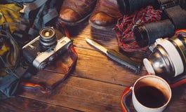 在木背景的旅行辅助部件 老远足的皮靴、背包、葡萄酒影片照相机、刀子和热水瓶 图库摄影