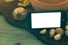 在木背景的智能手机用香料 库存照片