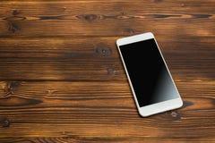 在木背景的智能手机 免版税库存照片
