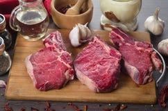 在木背景的未加工的新鲜的肉肋骨眼睛牛排构成 免版税库存照片
