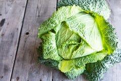 在木背景的未加工的皱叶甘蓝 有机食品 免版税库存照片