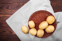 在木背景的未煮过的土豆 在一个棕色篮子的土豆肿胀在一块灰色布 健康土气菜 库存照片