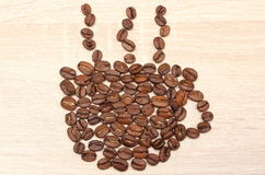 在木背景的杯形状的咖啡豆 库存图片