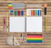 在木背景的桃红色笔记本和学校或者办公室工具 图库摄影