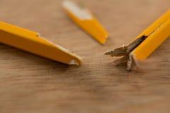 在木背景的残破的黄色铅笔 免版税库存图片