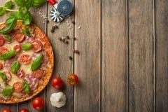 在木背景的比萨玛格丽塔酒,顶视图 比萨玛格丽塔用蕃茄、蓬蒿和无盐干酪乳酪 库存照片