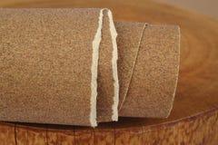 在木背景的沙纸 免版税图库摄影
