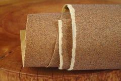 在木背景的沙纸 免版税库存图片