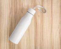 在木背景的浪端的白色泡沫瓶 被绝缘的容器为保留您的饮料 图库摄影