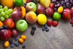 在木背景的混杂的新鲜水果用水滴下 免版税库存照片