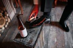 在木背景的清洁鞋子 有刷子的黑鞋子 红色可调扳手 婚姻白色的背景明亮的环形 背景啤酒瓶例证桔子向量 木头 免版税库存照片