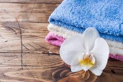 在木背景的温泉和健康概念 五颜六色的特里毛巾和一朵白色兰花开花 免版税库存照片