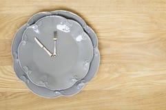 在木背景的灰色板材时钟 库存图片