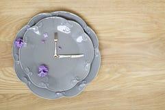 在木背景的灰色板材时钟 免版税库存图片