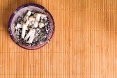 在木背景的烟灰缸 库存照片