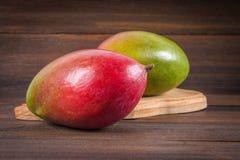 在木背景的热带水果芒果,整个或切 库存图片