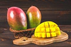 在木背景的热带水果芒果,整个或切 免版税库存照片