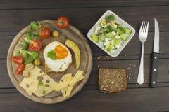 在木背景的煎蛋 煎蛋和菜在切板 免版税库存图片