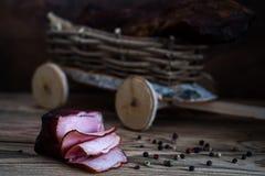在木背景的熏制的肉 库存照片
